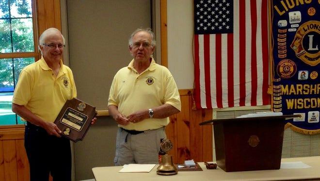 Tom Ptak, left, receives a plaque from President Lion Thomas Stram.