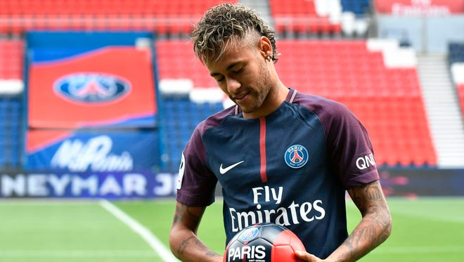 Neymar poses with a ball during his official presentation at the Parc des Princes stadium on Aug. 4, 2017 in Paris after agreeing a five-year contract with PSG.