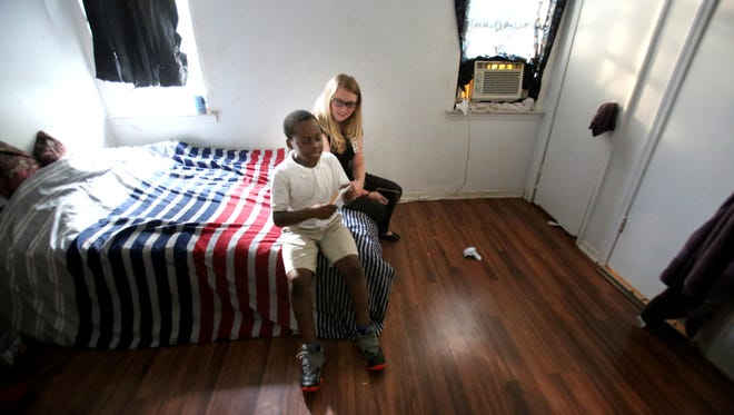 September 28, 2016 - Third-year law student Kelsey Walton sits with 8-year-old asthma sufferer Marquevius Hannah in his Frayser home. Asthma, a chronic and incurable illness that afflicts 12,000 Shelby County Schools students, is the single most common reason for admissions at Le Bonheur Children's Hospital.