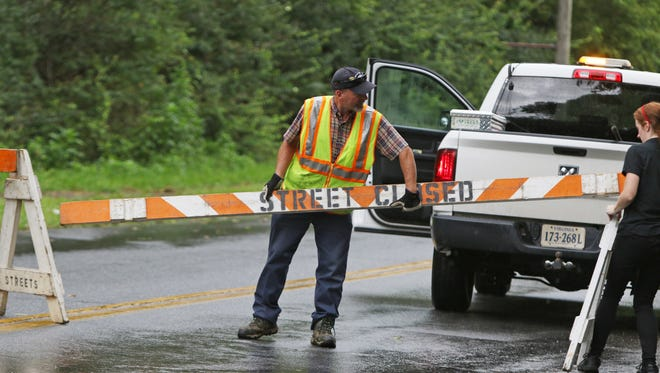 A public works employee replaces a barracade on Old Forest Drive on Friday, August 3, 2018 in Lynchburg.