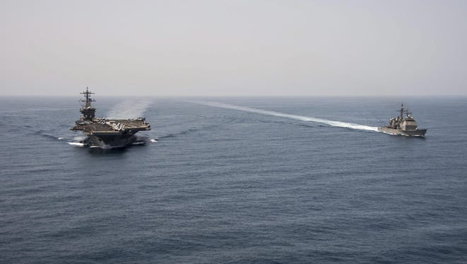 An aerial handout image from the US Navy showing the aircraft carrier USS Theodore Roosevelt and the guided-missile cruiser USS Normandy operating in the Arabian Sea on April 21.
