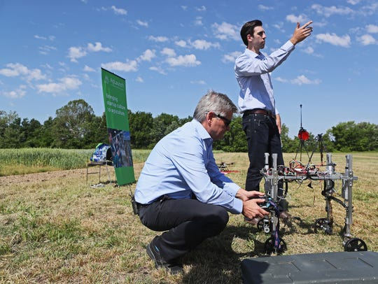 Billionaire investor Steve Case examines a robotic invention by Rabbit president and founder Zack James (right) during a Rise of the Rest bus tour in May at Agricenter International in Memphis, Tennnessee.