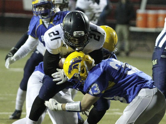 Newport Central Catholic's Peyton Davis makes a tackle against Lloyd in the playoffs last season.