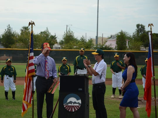 Tainan City, Taiwan Little League coach Jung Chin Hung (white shirt, applauding) presents Chandler City Councilman Jack Sellers with a hat during a ceremony at Diamondbacks Field at the Chandler Boys and Girls Club on Aug. 12, 2014. Hung said the hat says Victory. Woman in blue dress is Shen-Yi Michelle Change of the Taiwan Benevolent Association of Phoenix. She translated for Hung.