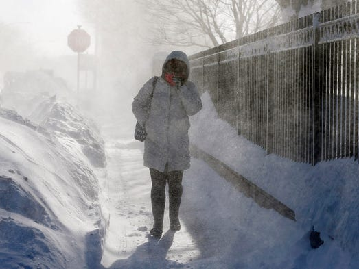 A woman walks through blowing snow in the East Boston