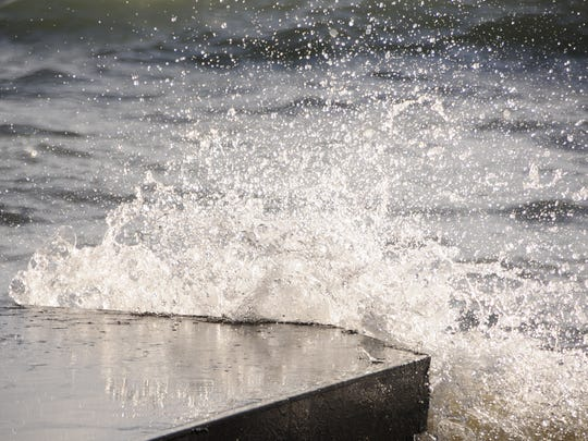 Waves break against a concrete slab in Lake Huron. High waves are expected today.