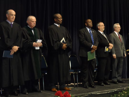 Standing during the Alexandria inauguration ceremony on Monday are (from left) Alexandria City Judge Richard Starling Jr., retired federal Judge F.A. Little Jr., retiring 9th District Judge Donald Johnson, Pineville Mayor Clarence Fields, Alexandria City Council President Chuck Fowler and the Rev. Lee Weems of Emmanuel Baptist Church.