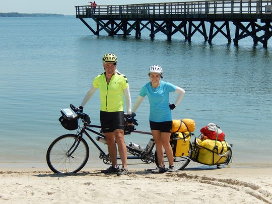 Dana Miller and his daughter, McKaylie, pose with their tandem bicycle rig's rear wheel in the waters of the Atlantic Ocean as they start out on their trip making their way across the United States on their tandem bicycle.