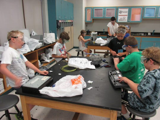 The camp invention engineers are taking apart old electronics