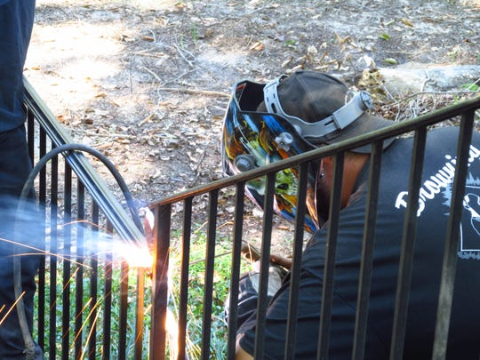 A workman makes repairs to a wrought iron railing damaged by a storm at the historic Kilgore-Lewis House.