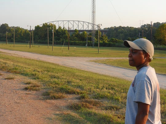 The O.K. Allen Bridge can be seen in the distance as Carolyn Turner awaits the bridge's demolition Saturday morning. The bridge was demolished at 8 a.m.