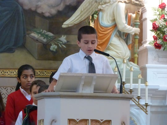 Fourth grade student, Justin Wistuba, shares those things his classmates are thankful for Thanksgiving during St. Stanislaus Kostka School's Annual Benefactor Mass which was held on Nov. 25