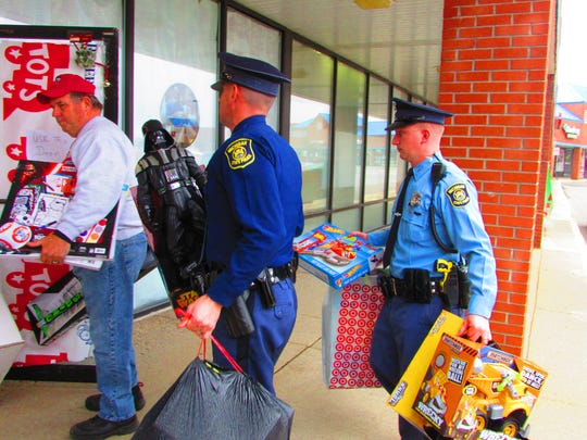 Michigan State Police Trooper Patrick Herman and Motor Carrier Officer Ryan Frost deliver toys Wednesday to the Toys for Tots program.