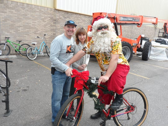Santa Claus (right), aka Tommy Webster, poses with Mike Hopkins of Red River Cyclery and Katie Hazmark before Sunday's bike ride in Alexandria to benefit Main Street Mission in Pineville.