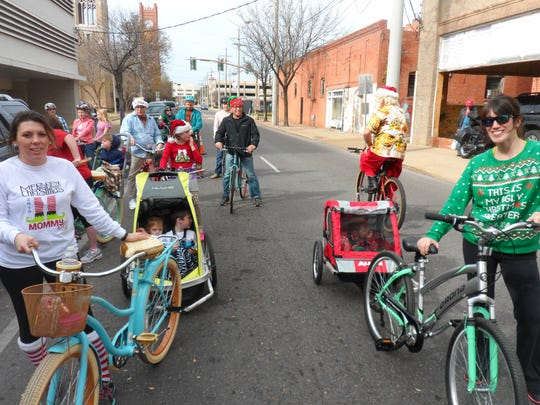 Maggi Pepiton (left), with her children, Sophie Moreau and Duncan DeSoto, in a bike trailer, awaits the beginning of the Christmas Cruiser Ride on Sunday along with Krystal Myrick (right), whose son, John-Everett, was in a bike trailer.