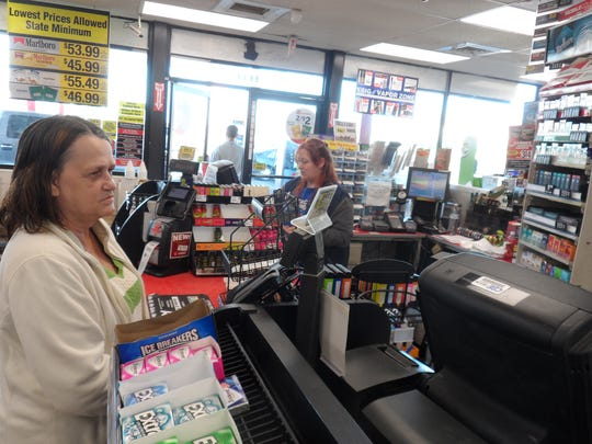 Donna McCall (left) of Pollock waits to get the Powerball tickets she purchased Sunday at the Circle K store in the Kingsville area of Pineville. In the background (right) is clerk Nealy Dempsay.