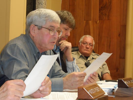 Grant Parish Police Juror Carl Ray Lasyone (foreground) reads the resolution opposing open burning. The Police Jury approved the resolution.