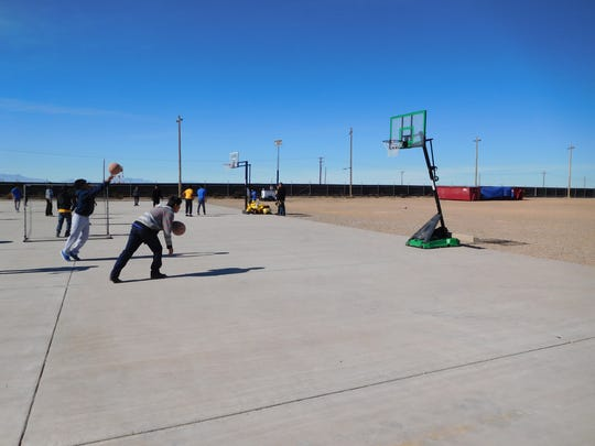 A group of unaccompanied children play basketball at