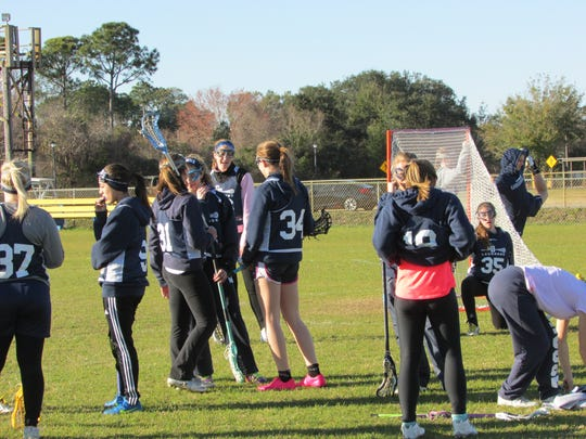 Members of the Gulf Breeze High girls varsity lacrosse team prepare for Friday's season-opening game.
