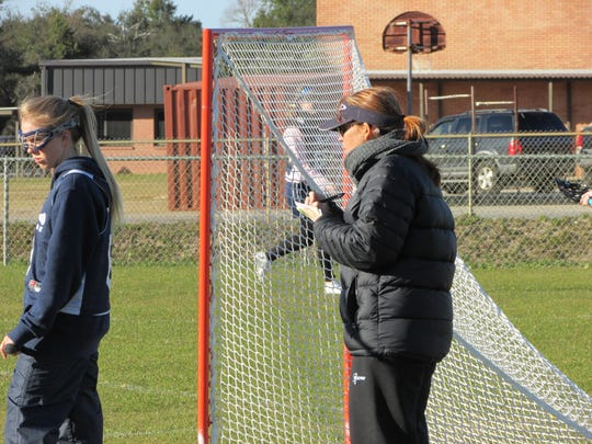 Gulf Breeze High girls lacrosse coach Carlee Costello watches her team practice Tuesday in preparation for Friday's season-opener.
