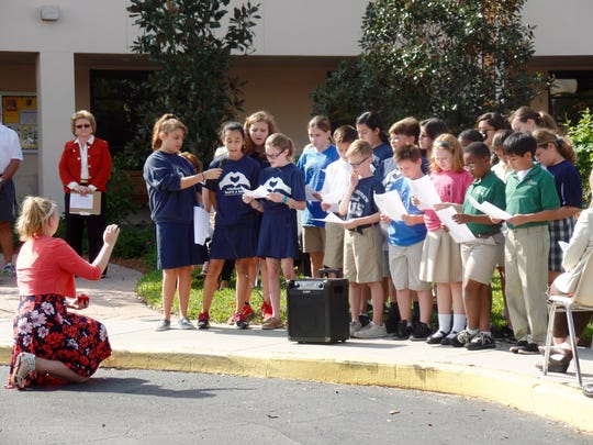 Children perform at the sculpture blessing at St. Andrews