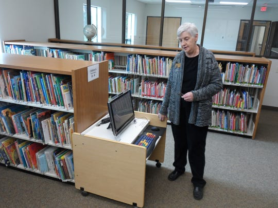 Mariann Strange, manager of the J.L. Robertson Branch Library in Tioga, looks at a computer in the new children's section of the  library, which reopened Monday following closure for renovation and expansion.