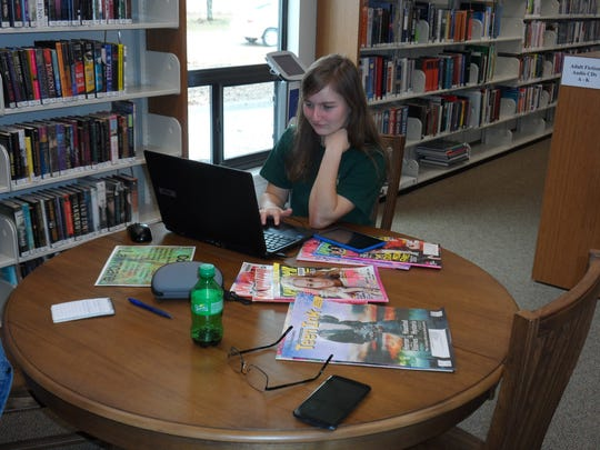 Dakota Ivey, 18, who is home-schooled, works on a laptop computer in the new teens section of the J.L. Robertson Library in Tioga on Monday.