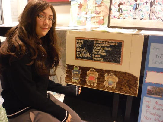 """On Feb. 4, Valerie Urbaez from Perth Amboy Catholic School, was honored at the State House in Trenton for winning third place in the """"Why New Jersey Needs Catholic Schools"""" Art Contest. Urbaez, picturted here with her winning poster, was given a tour of the State House, attended a legislative hearing and received her Award Certificate at a luncheon. She attended the ceremony with her father, Ricardo Urbaez and her art teacher, Rose Lavin Pennyfeather. The award was presented by Kim Chorba from the Diocese of Metuchen."""