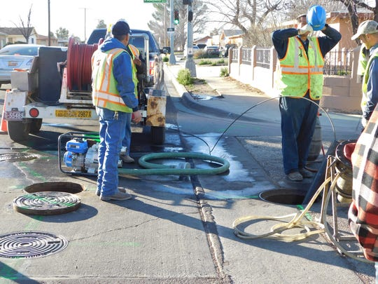Las Cruces Utilities workers repair an aging sewer pipe with the cured-in-place process at the corner of Alameda Boulevard and Madrid Road.