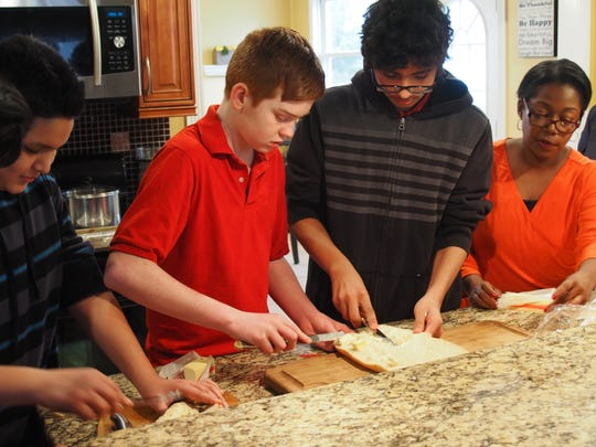 Left to right, Kenneth Velarde, Patrick Hickey and Rodrigo Lisboa work as a team to make some French bread with Bleu Cheese melt under the watchful eye of television producer and instructor Sonia Armstead.