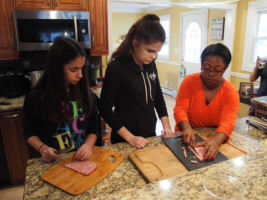 Left to right, Karina Campos and Kelly Tchorzewski watch as television producer and cooking expert Sonia Armstead instructs them on how to chop some ham for a skillet Cordon Bleu recipe.
