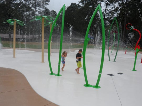 Camille Schneider (left), 5, and her brother, Evan, get wet as they walk through the new splash pad at Kees Park in Pineville on Friday.