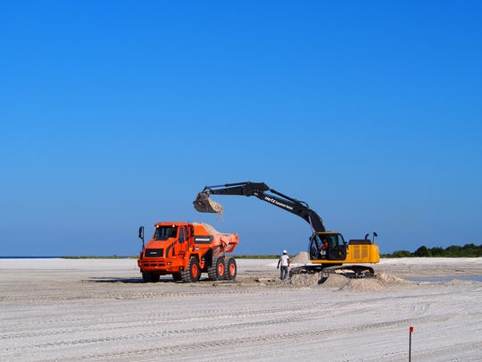 A bulldozer digs sand and places it along the dune line to increase the slope for better drainage.