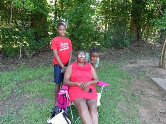 Linda Charles poses with two of the four grandchildren