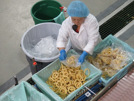 An employee at Monogram Appetizers' Moore Road facility in Plover works on the onion line.