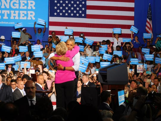 Democratic presidential candidate Hillary Clinton and President Barack Obama hug during a campaign rally in Charlotte Tuesday.