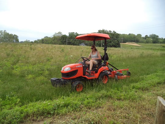 Fern Truitt, Arc staffer, mows at the Junction Earthworks site to prepare the property for Saturday's event.