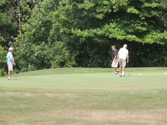 Chuck Snyder  (left), Pudge Hargis (center) and Roger Sturgeon putt out on Friday afternoon at the Golf Club of Bucyrus. The group also played with Ralph Ehrhart, who is not pictured.