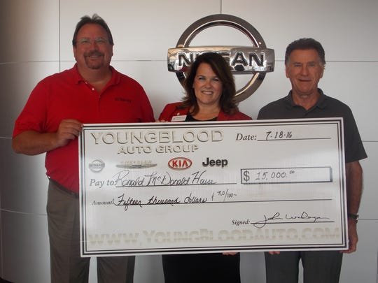 Bonnie Keller, President and CEO of RMHC, received the donation from owner John Youngblood and General Manager John Widiger