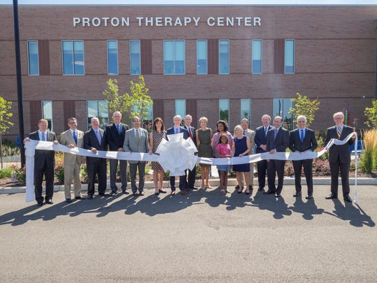 Dignitaries line up with the ribbon to cut in opening the new proton therapy center at the Liberty campus of Cincinnati Children's Hospital Medical Center in 2016.