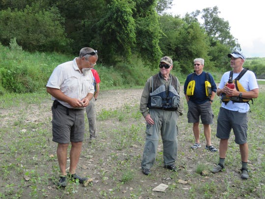 Naturalist Chris Adkins, left, summons stories of the river to a group of paddlers on the Raccoon River Aug. 20.