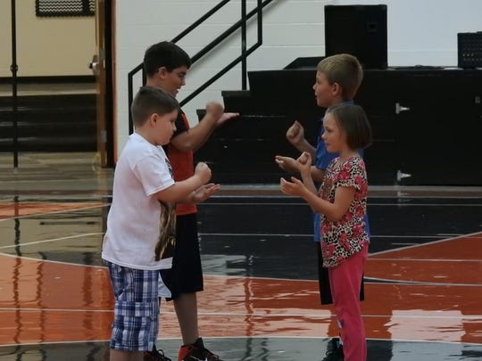 Ridgewood Middle School fourth-graders play rock-paper-scissors Tuesday to determine which group will perform the next round of exercises in gym class.