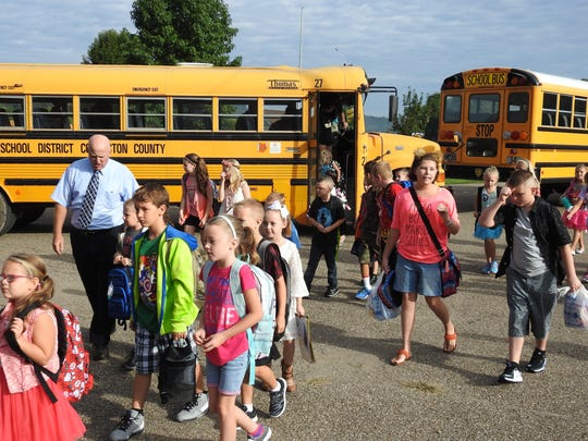 Principal Joel Moore accompanies students from the bus to the school on their first day of classes at Conesville Elementary School Wednesday.