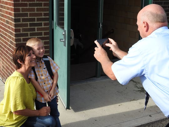 Principal Joel Moore takes a photo of new kindergartner Noah Chaney and his mother Amanda Chaney on Noah's first day of school.
