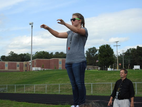 Field Commander Makenna Graves, 17 and a senior, conducts the Coshocton High School Marching Band during rehearsal Wednesday, the first day of the new school year. Band director Barry Hardesty, right, looks on.