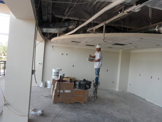 A worker on stilts works on the ceiling in a corridor area at the Rapides Parish Coliseum on Wednesday while a group was touring the building to see the progress of renovation.
