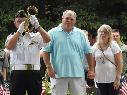 Craig and Julie Border, of Keene, listen to taps after