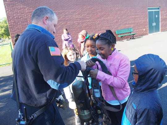 On Oct.14th Third grader Le'yonnah Walton of School No.5 gets a firsthand experience on how heavy the fire equipment can be.