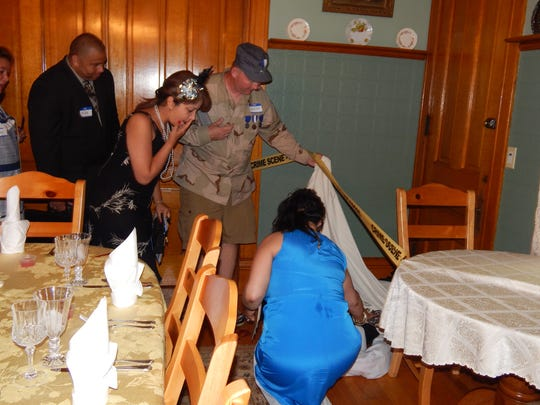 "Guests investigate a ""corpse"" during a Murder Mystery Weekend at Victorian Dreams B&B in Lodi."