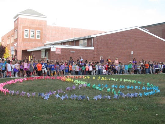"Students at Whitehouse School stand beside the ""Pinwheels"